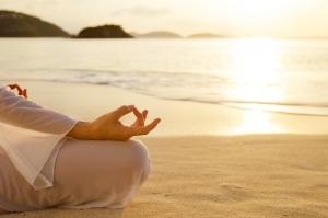 woman meditating at sunset on the Caribbean beach