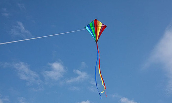 Rainbow kite flying on a string with a blue cloudy sky, Hampshire, England, U.K