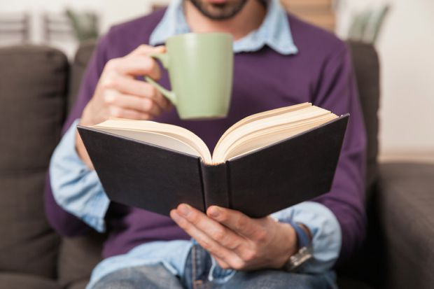 man-drinking-coffee-and-reading-book